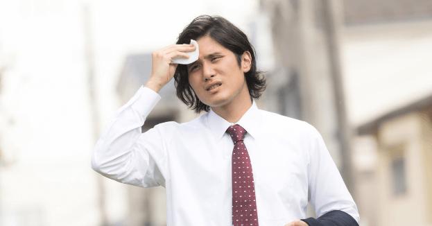 汗をぬぐう男性